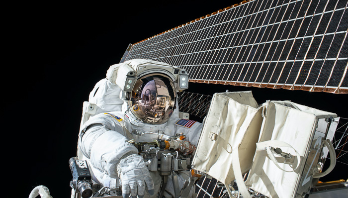 Astronaut doing some repairs outside the International Space Station (ISS). Zero gravity. Universe.