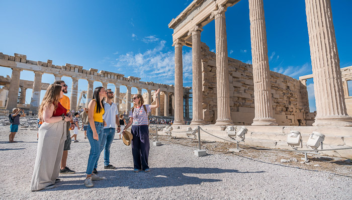Three women and two men are in front of some ancient ruins in the Acropolis,Athens,Greece.