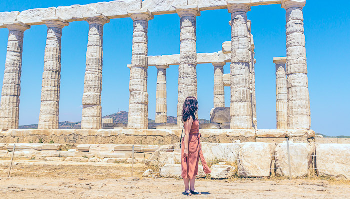 A woman with an orange dress in front of a temple. Greece.