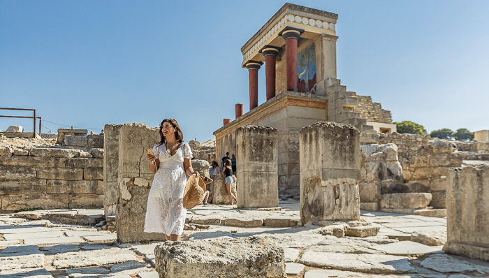 A woman with a white dress and holding a hat walks around the Acropolis with an audio guide.