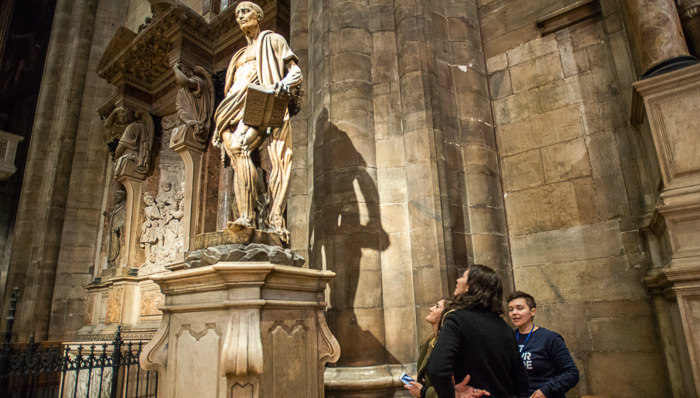 Mystery, statue of St. Bartholomew. Tourists learning about the martyr during a tour of the Milan Duomo.