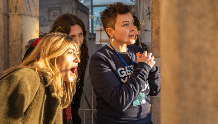 3 happy friends looking out the window of the Milan Duomo, Italy, and smiling. A beautiful day to enjoy great beauty.
