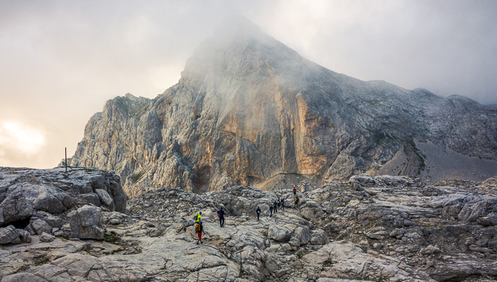 A group of people are walking towards the Mount Olympus, Greece.