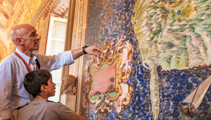 A guide explains a painting to a kid in the Vatican Museums, Rome.