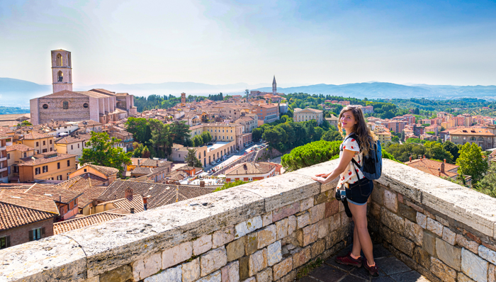 View in Perugia, Italy in Umbria cityscape of Church of San Domenico tower and rooftops of town village in summer landscape with woman at overlook
