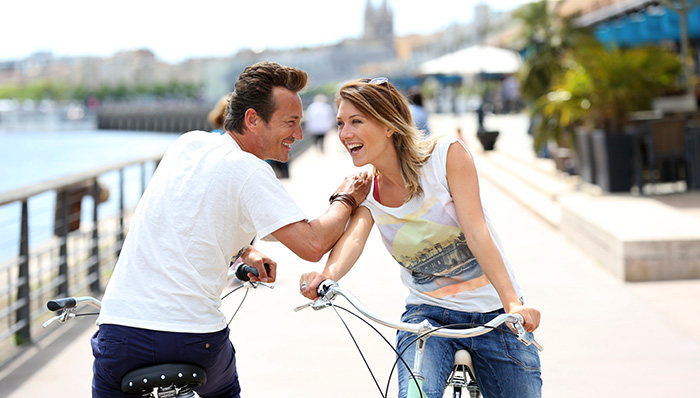 Man and woman on bikes chatting. Acquaintances bump into each other during a casual ride in Bordeaux, France.