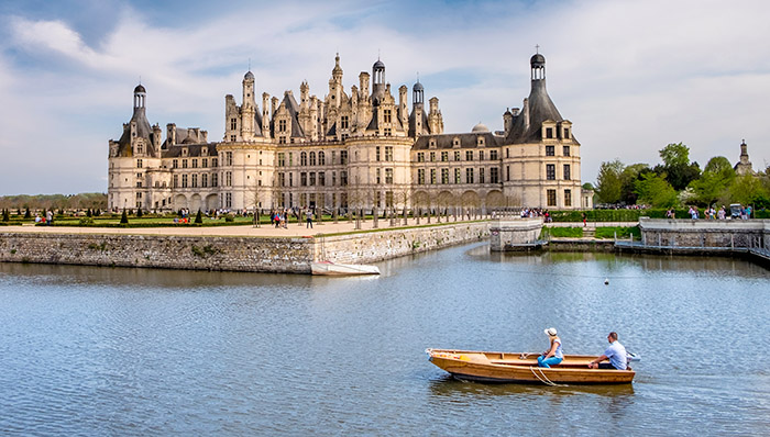 2 people cruising. Rowing boat. French castle / palace in Loire Valley, France.