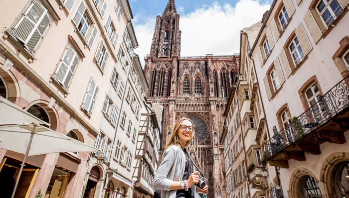 Woman photographing lovely buildings in Strasbourg old town. Strasbourg cathedral.