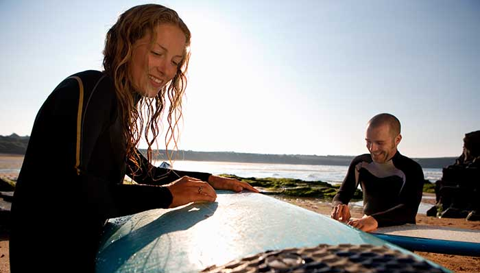 Woman and man on wetsuits getting ready for some surfing, SUP, standup paddle. Waxing their surfboards paddle board.