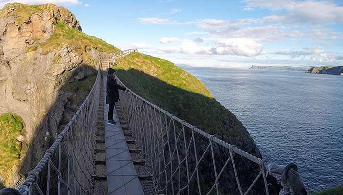Visiting Game of Thrones' Carrick-a-Rede Rope Bridge. Woman standing in the middle of it.