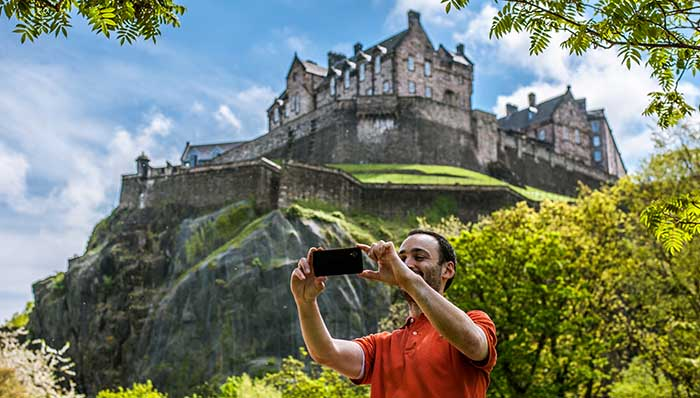 Guy taking a selfie with a castle on top of a hill in the background.