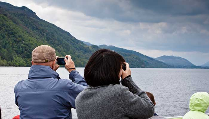 2 elderly people along with other tourists taking pictures on a boat in the Loch Ness, Glasgow, UK.