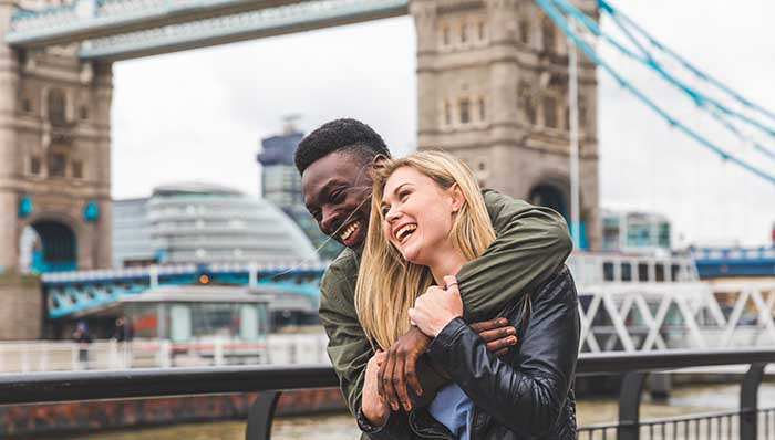 Young couple hugging in excitement at the London Bridge, London, UK.