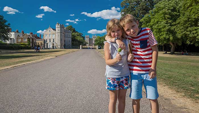 Young siblings posing for a photo on the street road that leads to Windsor Castle. UK.