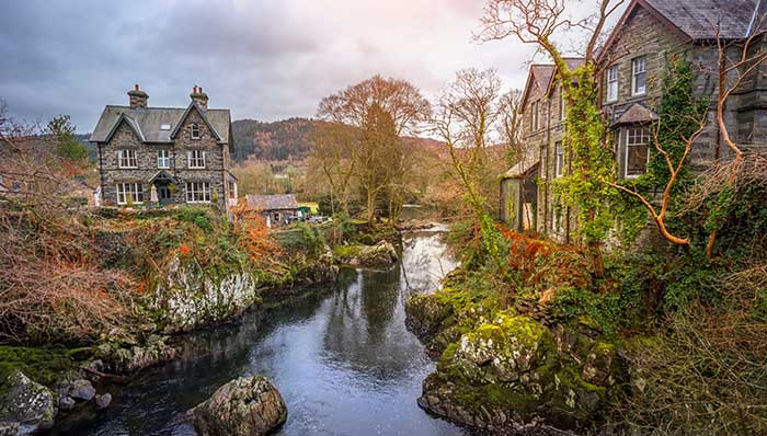 Cozy stone houses on the shore of a brook, water stream, water course.