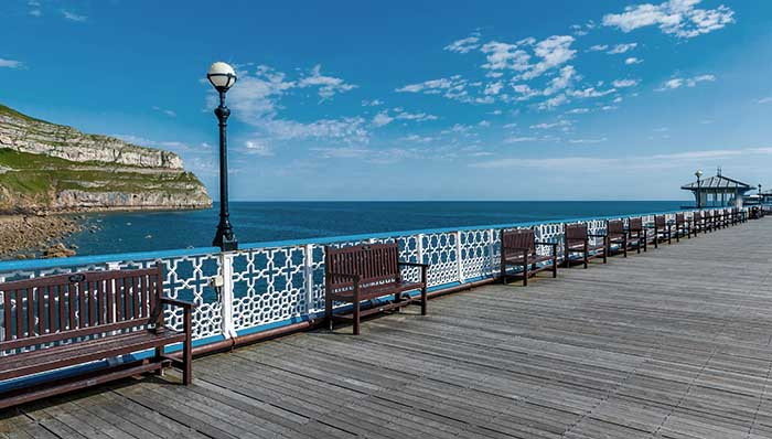 Lovely wooden pier with benches near a beach and the cliff.