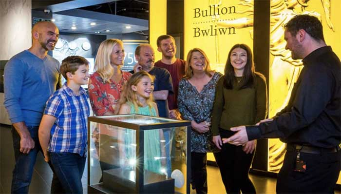 Group of children and adults being entertained by a guide by a glass display showcase during a visit.