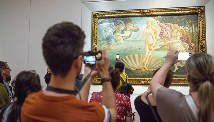 People at the Uffizi Gallery taking pictures of the famous Botticelli's The Birth of Venus.