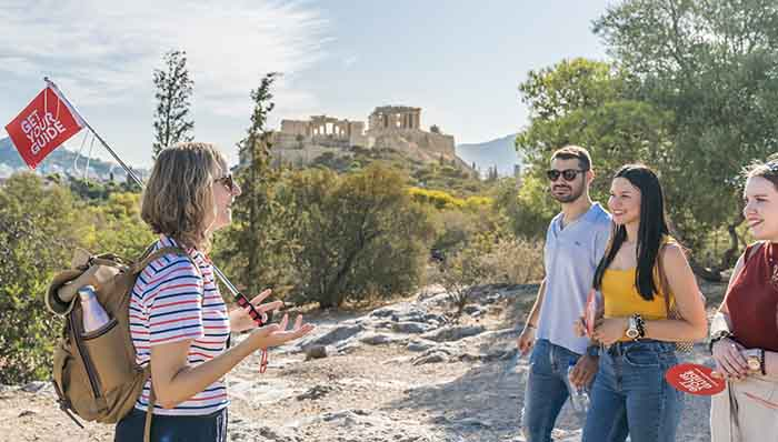 The best of a guided tour: GetYourGuide guide with a flag taking the group on a trip through the history of Ancient Greece heading to the Acropolis of Athens.