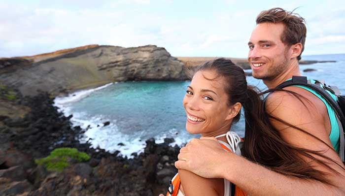 Summer explorers: young adventurous couple on a hike smiling for a picture with a tropical rocky beach in the background.