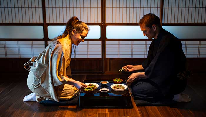 Japanese food and tea tradition. Young couple dressed on a kimono (Japanese robe) in a typical Japanese house using Hashi (Japanese chopsticks).