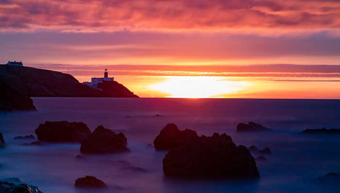 Shy sun on a winter solstice day. View from a cliff looking at rocks standing tall above sea level and a lighthouse.