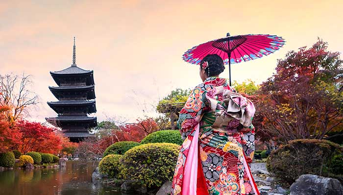 Woman on typical Japanese outfit looking at a pagoda across a lake surrounded by trees with red leaves.