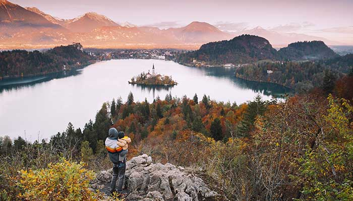 Man carrying a baby on his arms standing on top of a rock overlooking a lake with mountains in the background.