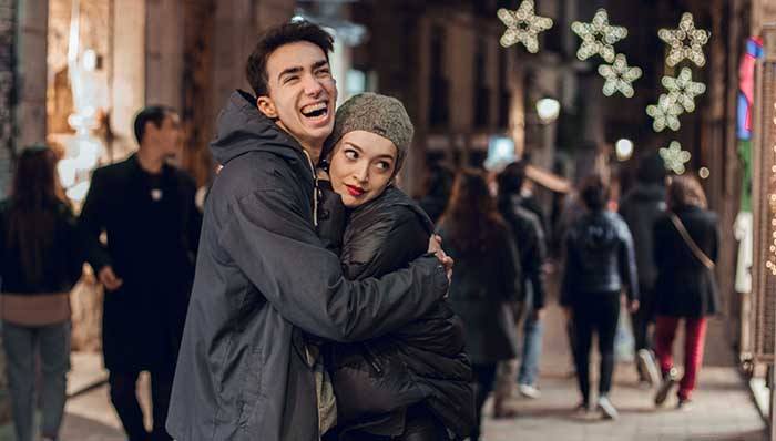 Couple on a hug laughing on the streets.