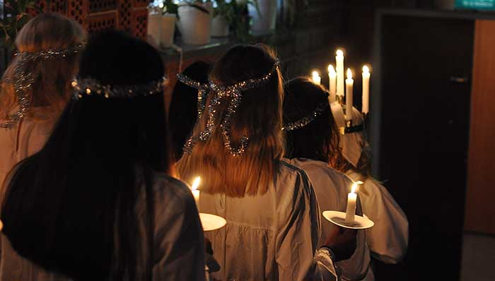 Women dressed in typical white outfit parading with candle lights on a celebration.