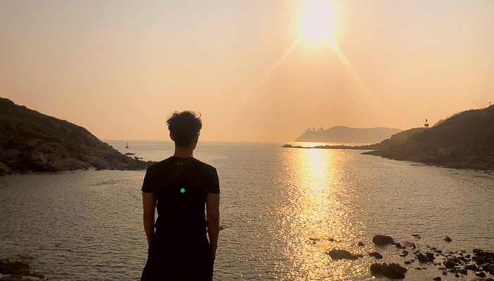 Guy standing by the seashore with a beautiful sunset in Hong Kong.
