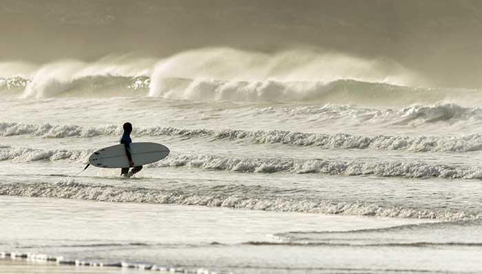Surf as a way of life. Man on wetsuit with a surfboard walking into the sea and reaching for the waves.
