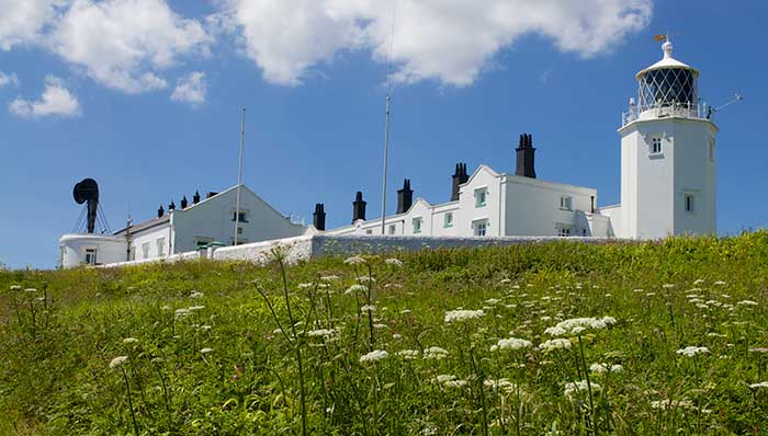 White lighthouse building uphill on a day with clear skies.
