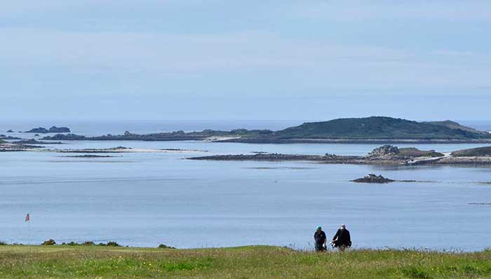 Where the meadows meet the sea: 2 people reach to the shore with many small islands in the background.