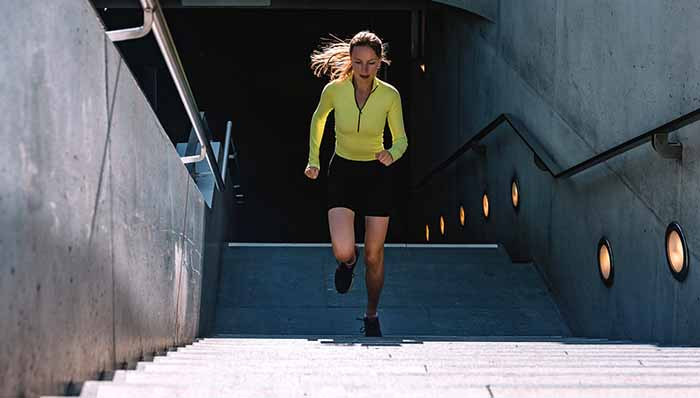 young sports woman running up stairs from subway sation