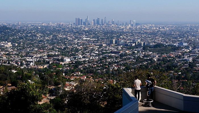 View of the city of los Angeles, US, from the Griffith Observatory. 2 people at a scenic viewing point.