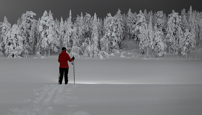 Hiker wearing snow shoes, walking across a snow covered tundra in a wild winter landscape at night.