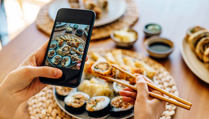 Person taking photo of a sushi plate with smartphone