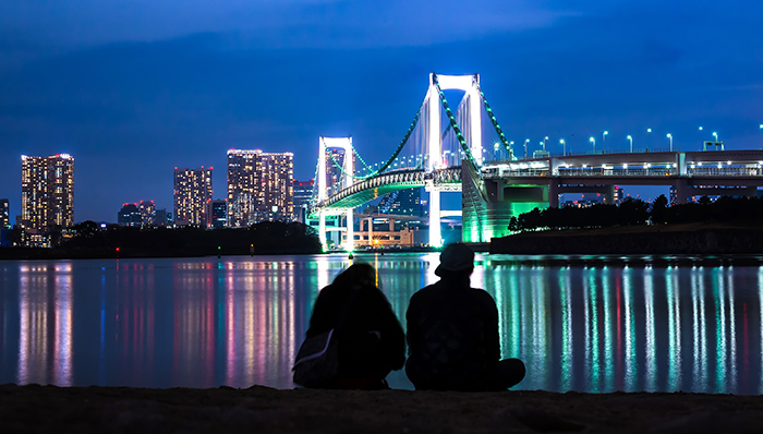 Light of Rainbow bridge at night and Tokyo tower with Couple Sit beside the beach