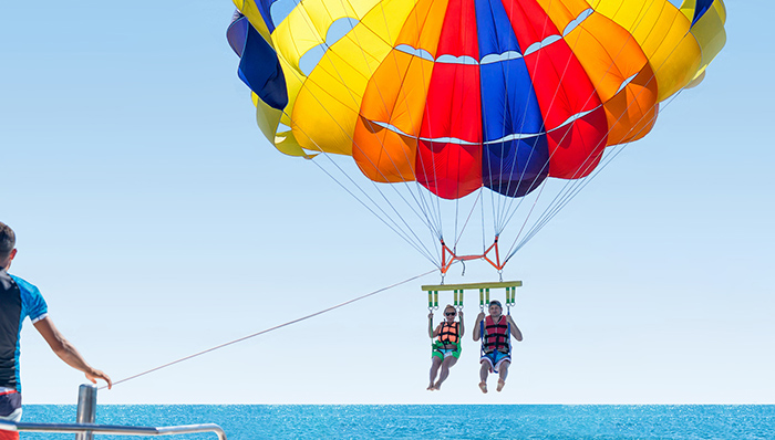 Smiling couple Parasailing on Tropical Beach in summer under parachute hanging mid air. Having fun. Tropical Paradise. Positive human emotions.