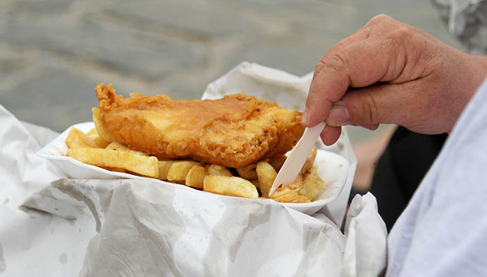 man eating fish and chips takeaway in paper