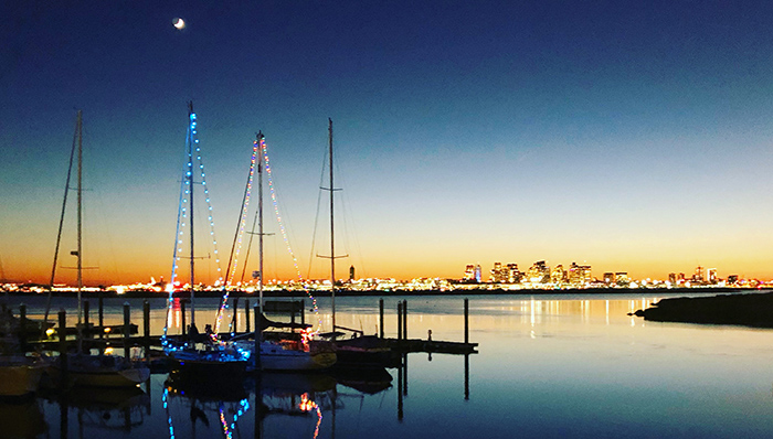 Lights adorn two sailboats in Boston Harbor as the sun sets leaving a beautiful reflection