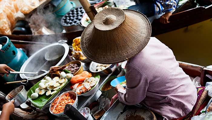 Asian Food vendor at the Damnoen Saduak Floating Market near Bangkok. Lady is selling traditional thai food from her boat.