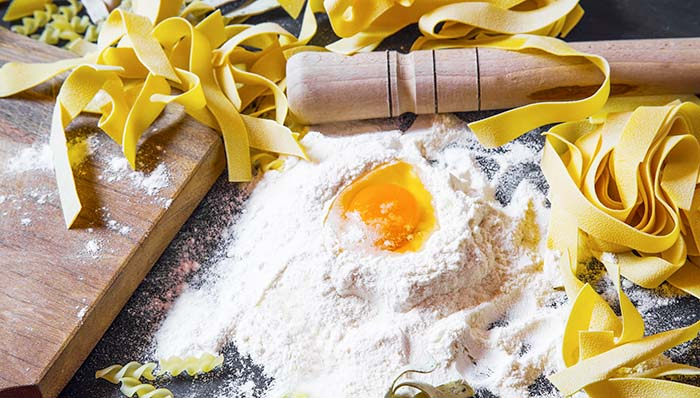 Homemade pasta with white wheat flour and egg on black background
