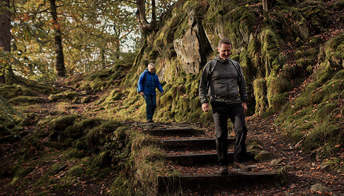 Front shot of a couple social distancing while walking on a path in the Lake District.