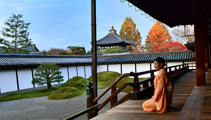 A Japanese woman in kimono is appreciating Japanese rock garden at Hojo (the former living quarters of the head priest) of Tofuku-ji Temple in Kyoto. This garden is called Eastern Garden, the largest of the four gardens surrounding Hojo and it is composed of four rock groups symbolizing Elysian islands on the rough seas.