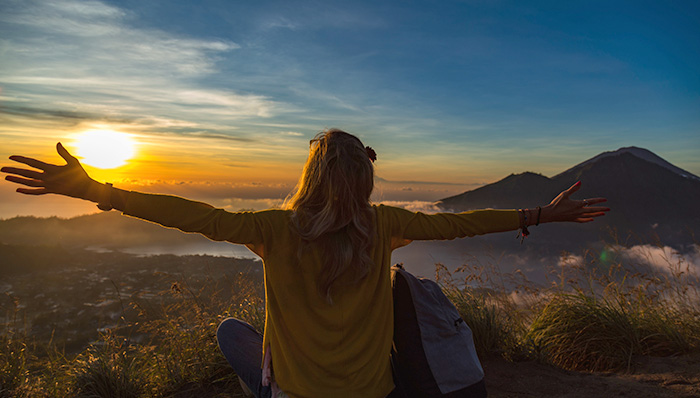 woman standing on top of mount batur at sunrise watching the city below