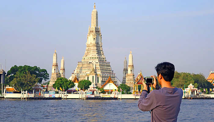 man photographing at temple against buildings while on a cruise