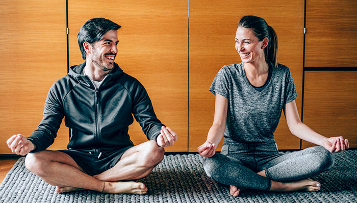 Couple s'amusant en pratiquant le yoga au sol.