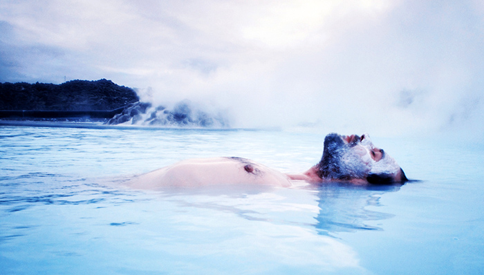 Man floating in the Blue Lagoon, Iceland. The lagoon is fed by the water output of the nearby geothermal power plant Svartsengi. The waters are rich in minerals and combined with the natural algae give it the distinctive color and is reputed to help some people suffering from skin ailments.